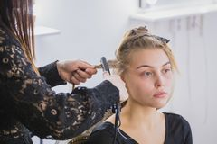 Beautiful young woman is getting her hair straightened at beauty saloon royalty free stock photo