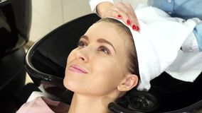 Beautiful young woman getting her wet hair wrapped in a towel by a professional hairdresser royalty free stock photos