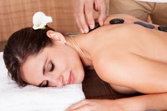 Beautiful young woman getting hot stone therapy. At spa salon Royalty Free Stock Photo
