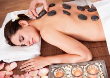 Beautiful young woman getting hot stone therapy. At spa salon Royalty Free Stock Image