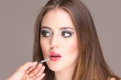 Beautiful young woman getting makeup done Stock Photo