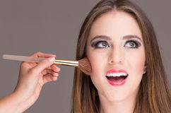 Beautiful young woman getting makeup done Royalty Free Stock Images