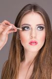 Beautiful young woman getting makeup done Stock Photos