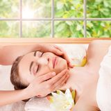 Beautiful young woman getting spa massage. Beautiful Young Woman Getting Massage Facial and Body in Spa Salon. Treatment Cosmetics Beauty Care Body Herbs royalty free stock image
