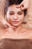 Beautiful young woman getting spa massage. Eautiful young relaxed woman enjoy receiving face massage at spa saloon Stock Photo