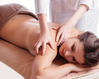 Beautiful young woman getting spa massage. Eautiful young relaxed woman enjoy receiving face massage at spa saloon Royalty Free Stock Photo