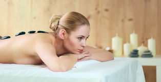 Beautiful young woman getting spa massage, lying on salon Royalty Free Stock Images