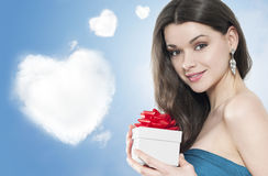 Beautiful young woman with a gift. Beautiful young woman with a gif dreaming what's inside stock photography