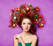 Beautiful young woman with gifts, candies, baubles and cones in Royalty Free Stock Images