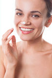 Beautiful young woman girl applying cream on her face isolated Royalty Free Stock Images