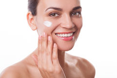 Beautiful young woman girl applying cream on her face isolated Stock Image