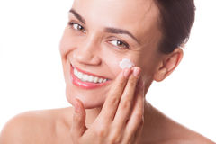 Beautiful young woman girl applying cream on her face isolated Stock Photo