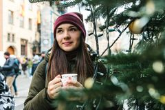 A beautiful young woman is drinking from a mug a hot drink. A beautiful young woman or girl is drinking from a mug a hot drink next to a Christmas tree during Stock Photo