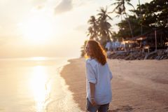 Beautiful young woman girl with flying curly hair on the background of a tropical beach at sunset, beauty, freedom, pleasure, joy royalty free stock images