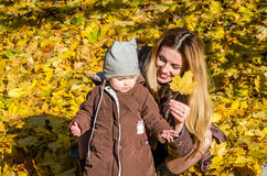 Beautiful young woman girl happy mother playing with her daughter smiling and holding a yellow maple leaves walking in autumn park Royalty Free Stock Image