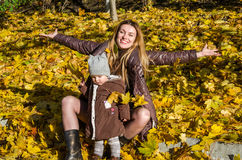 Beautiful young woman girl happy mother playing with her daughter smiling and holding a yellow maple leaves walking in autumn park Stock Photos
