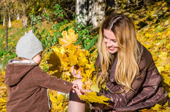 Beautiful young woman girl happy mother playing with her daughter smiling and holding a yellow maple leaves walking in autumn park Royalty Free Stock Photos