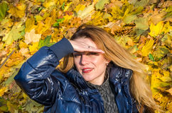 Beautiful young woman girl happy mother playing with her daughter smiling and holding a yellow maple leaves walking in autumn park Stock Image