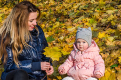 Beautiful young woman girl happy mother playing with her daughter smiling and holding a yellow maple leaves walking in autumn park Stock Images