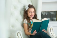 Beautiful young woman  girl reading a book. Beautiful young woman with a bow on her head girl reading a book Stock Image