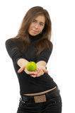 Beautiful young woman gives green apple. Royalty Free Stock Image