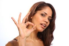 Beautiful young woman gives ok sign to camera Royalty Free Stock Image