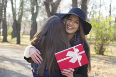 Beautiful young woman giving a gift to her friend Royalty Free Stock Photo