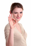 Beautiful young woman giving ok sign and winking Royalty Free Stock Photography