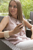 Beautiful young woman with glass of red wine sitting on chair outdoors Stock Photography