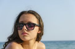 Beautiful young woman with glasses and bikini sitting on beach stock images