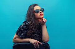 Beautiful young woman in glasses on the black vintage dress. Portrait of the beautiful young woman in glasses on the black vintage polka dot  dress on the blue Stock Images