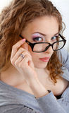 Beautiful young woman with glasses in grey Stock Images