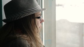 Beautiful young woman with glasses and hat looking out the window stock video footage
