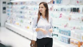 Beautiful young woman goes and looks at goods in cosmetics shop, slow motion stock video footage