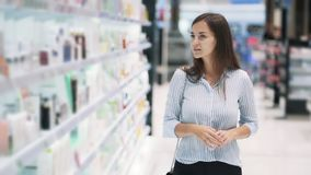 Beautiful woman goes among shelves in cosmetics shop, slow motion. Beautiful young woman goes among shelves and looks at goods in cosmetics shop, slow motion stock video footage