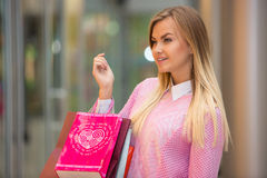 Beautiful young woman goes shopping in mall Royalty Free Stock Image
