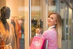 Beautiful young woman goes shopping in mall Royalty Free Stock Photography