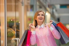 Beautiful young woman goes shopping in mall Stock Photos