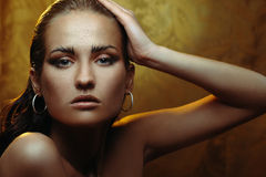 Beautiful young woman with gold makeup Royalty Free Stock Images