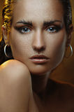 Beautiful young woman with gold makeup and bronze skin Stock Photo