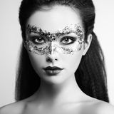 Beautiful young woman in gold mysterious mask Royalty Free Stock Photo