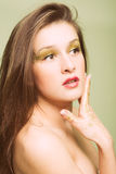 Beautiful young woman with golden eye makeup and Royalty Free Stock Images