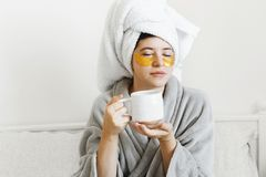 Beautiful young woman with golden eye patches and in bathrobe holding cup of coffee and lying in bed, enjoying morning routine. Happy girl with coffee cup and royalty free stock photo
