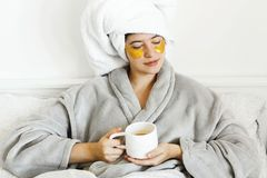 Beautiful young woman with golden eye patches and in bathrobe holding cup of coffee and lying in bed, enjoying morning routine. Happy girl with coffee cup and stock image