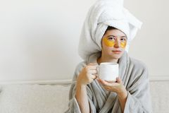 Beautiful young woman with golden eye patches and in bathrobe holding cup of coffee and lying in bed, enjoying morning routine. Happy girl with coffee cup and stock photography