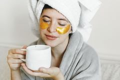 Beautiful young woman with golden eye patches in bathrobe holding cup of coffee and lying in bed, enjoying morning routine. Happy. Girl drinking coffee and royalty free stock image