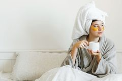 Beautiful young woman with golden eye patches in bathrobe holding cup of coffee and lying in bed, enjoying morning routine. Happy. Girl drinking coffee and stock images