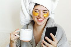 Beautiful young woman with golden eye patches in bathrobe holding cup of coffee, lying in bed and looking at phone screen. Enjoying morning concept. Happy girl stock photography