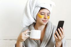 Beautiful young woman with golden eye patches in bathrobe holding cup of coffee, lying in bed and looking at phone screen. Enjoying morning concept. Happy girl stock image