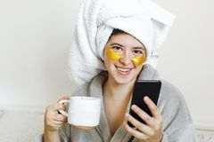 Beautiful young woman with golden eye patches in bathrobe holding cup of coffee, lying in bed and looking at phone screen. Enjoying morning concept. Happy girl royalty free stock photo